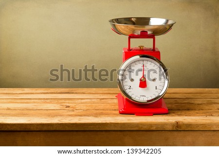 Retro style scales on wooden table over grunge background - stock photo