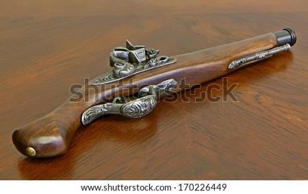 Retro style souvenir gun on oak-wood table. - stock photo