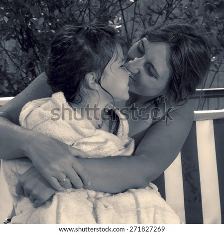 Retro style special toned photo of little girl and her mother in the summer garden hugging and kissing on a swing - stock photo