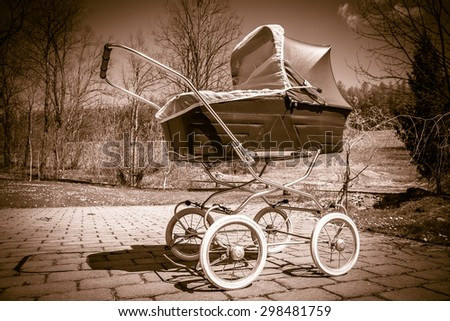 Retro style stroller baby carriage outdoors in nature on sunny day with old sepia filter - stock photo