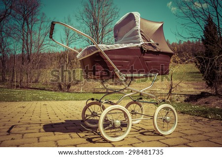 Retro style stroller baby carriage outdoors in nature on sunny day with retro vintage green instagram like filter - stock photo