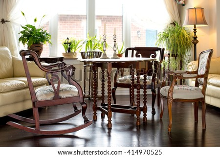 Retro style tea table setup in family room, against large windows. Antique furniture (walnut table from 1930s, vintage chairs, side table, flower stand).interior design. - stock photo