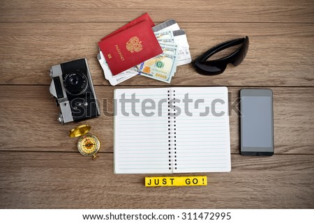 Retro style travel stuff on wooden table - stock photo