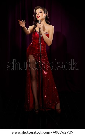 Retro style woman singer with microphone - stock photo