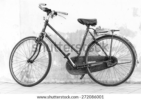 Retro styled black and white image of old bicycle isolated on a white wall background.
