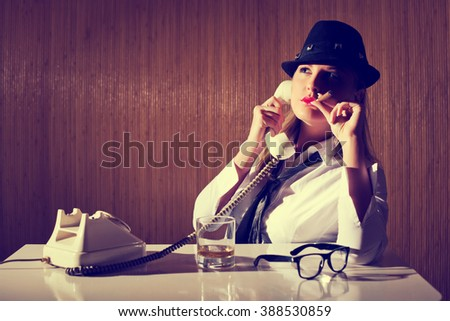 Retro styled businesswoman smoking cigar and talking on telephone. Image is intentionally toned. - stock photo