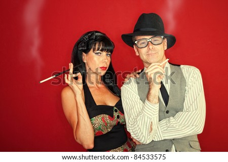 Retro-styled Caucasian couple smoke cigarette over maroon background