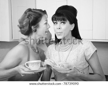 Retro styled Caucasian woman shares a secret with her friend - stock photo
