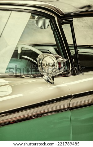 Retro styled detail of a vintage white with green car - stock photo