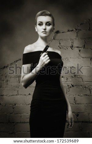 Retro styled fashion portrait of a woman with revolver in hand - stock photo