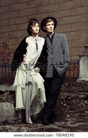 Retro styled fashion portrait of a young couple. Clothing and make-up in 1920s style. - stock photo