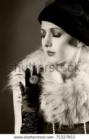 Retro styled fashion portrait of a young woman in gloves. Clothing and make-up in vintage style - stock photo