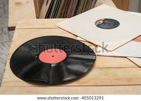 Retro styled image of a collection of old vinyl record lp's with sleeves on a wooden background. Browsing through vinyl records collection. Music background. Top view. Copy space. - stock photo