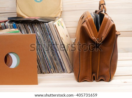 Retro styled image of a collection of old vinyl record lp's with sleeves on a wooden background.   Copy space. - stock photo