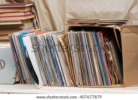 Retro styled image of a collection of old vinyl record lp's with sleeves on a wooden background. Top view.  Copy space. - stock photo