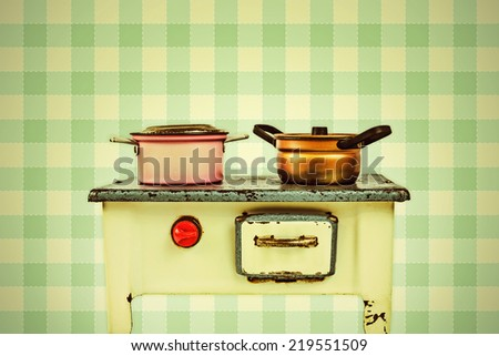 Retro styled image of a doll house cooking stove with pans in front of vintage wallpaper