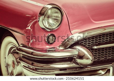 Retro styled image of a front of a pink classic car - stock photo