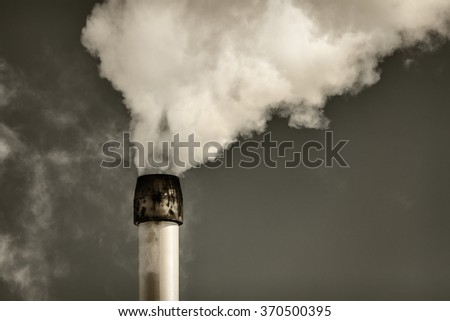 Retro styled image of air pollution from a factory pipe