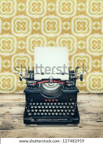 Retro styled image of an old typewriter on a wooden floor with vintage wallpaper behind it - stock photo