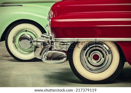 retro styled image of two vintage American cars parked next to each other - stock photo