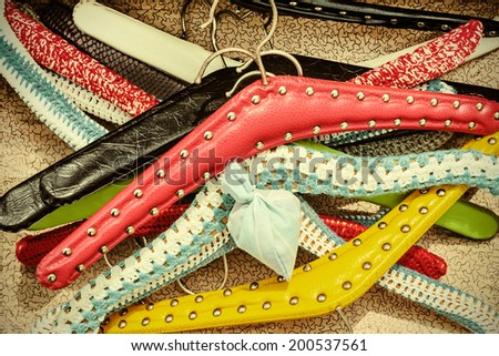Retro styled image of various colorful vintage dress hangers - stock photo