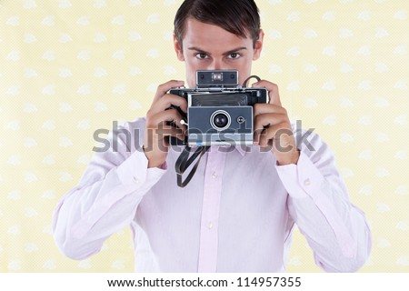 Retro styled man holding a medium format old style camera