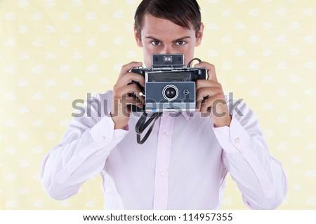 Retro styled man holding a medium format old style camera - stock photo