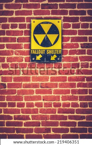 Retro Styled Nuclear Fallout Shelter Sign On A Red brick Wall - stock photo