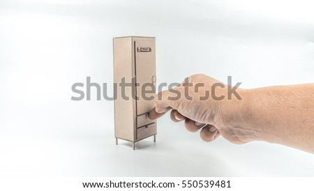 Retro styled or retro color hand holding miniature of wooden cupboard furniture. Concept of storage or interior management. Slightly de-focused and close-up shot. Copy space.