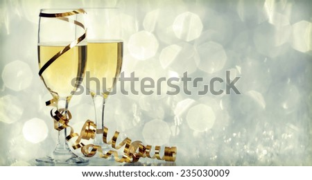 Retro styled photo of glasses with champagne on sparkling background