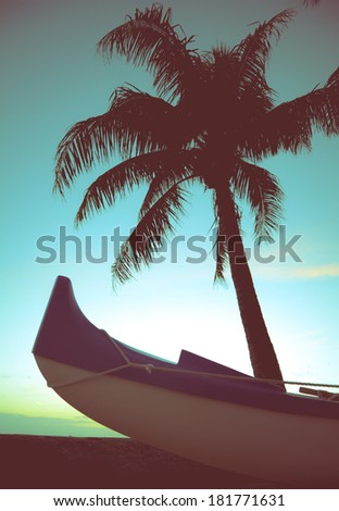Retro Styled Photo Of Outrigger Canoe And Palm Tree In Hawaii - stock photo