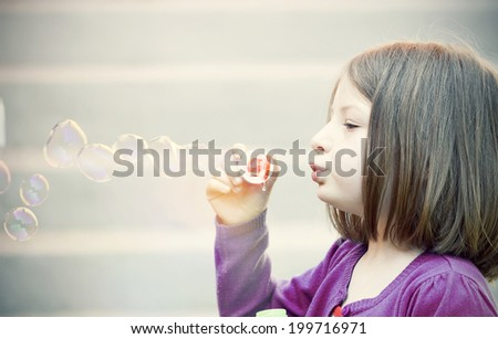 Retro styled photo of young girl blowing soap bubbles - stock photo
