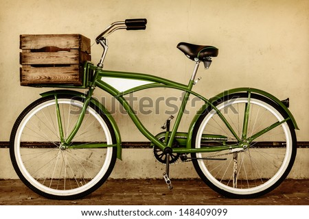 Retro styled sepia image of a vintage beach cruiser bicycle with wooden crate - stock photo