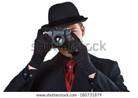 Retro 1940 stylephotographer wearing a hat and holding a vintage camera - stock photo