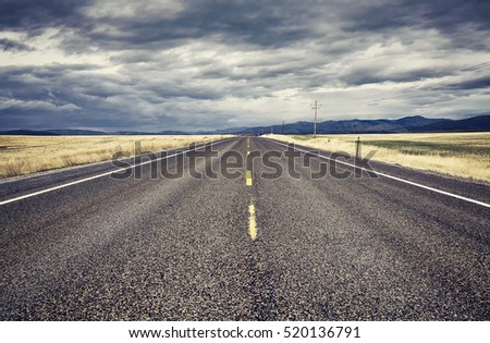 Retro stylized empty rural road with rainy clouds, USA.
