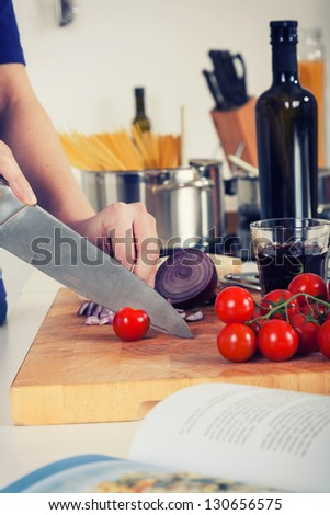 retro stylized image of ingredients for pasta and hands chopping tomatos - stock photo