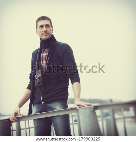retro stylized photo of photographer with vintage camera on a pier - stock photo