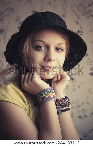 Retro stylized portrait of beautiful blond teenage girl in black hat and rubber loom bracelets. Vintage toned photo filter, instagram style effect - stock photo