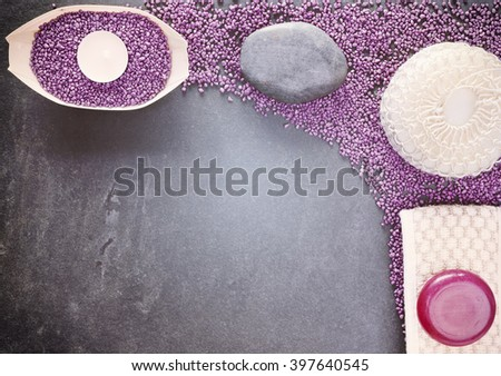 Retro stylized spa set with sponge, soap, towel, stone and candle over slate background, copy space, shallow depth of field. - stock photo
