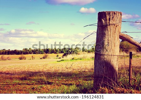 Retro sunset filter style country side scene with old gate post and barb wire. Taken at Barossa Valley, South Australia. - stock photo