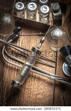 Retro syringe, stethoscope and medical cupping glass on a wooden table. Shallow depth of field. - stock photo