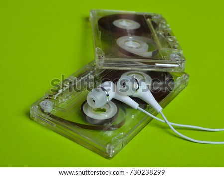 Retro technology. Plastic transparent audio cassette and white vacuum headphones on a bright green background. 80s.