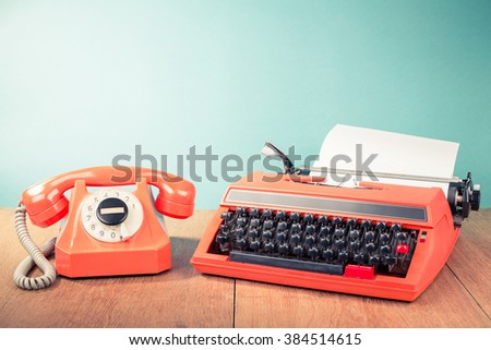 Retro telephone and old typewriter on table front mint green background. Vintage style filtered photo
