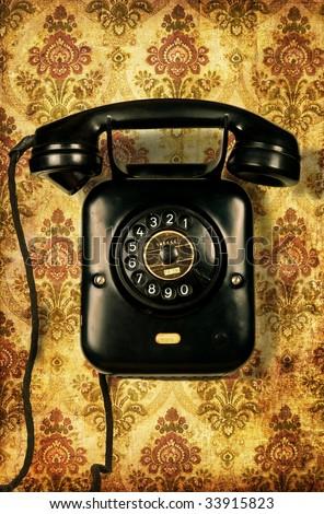Retro telephone on retro wallpaper - stock photo