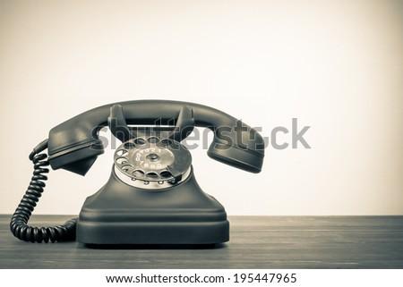 Retro telephone on table vintage style sepia photo - stock photo