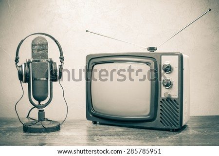 Retro television, old microphone from 50s and headphones. Vintage style sepia photo