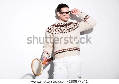 Retro tennis fashion man with black glasses holding a vintage wooden racket. Studio shot against white. - stock photo