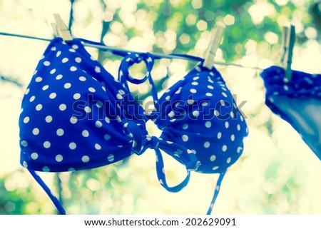 Retro toned polka dot bikini on clothesline  - stock photo
