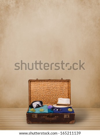 Retro tourist luggage with colorful clothes and copyspace on grungy background - stock photo