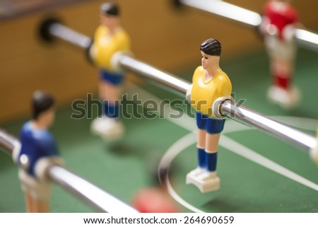 Retro toy football or soccer player suspended on a movable metal rod in a vintage board game, selective focus to one player - stock photo